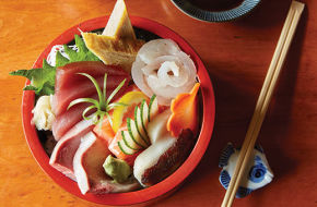 A bowl of chirashi—raw fish, vegetables, tamago (cold, sweet omelet) over rice.