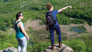 Reporter Joanna Buffum, right, points west toward Hackettstown from the heights of the Highland Trail through Allamuchy State Park.