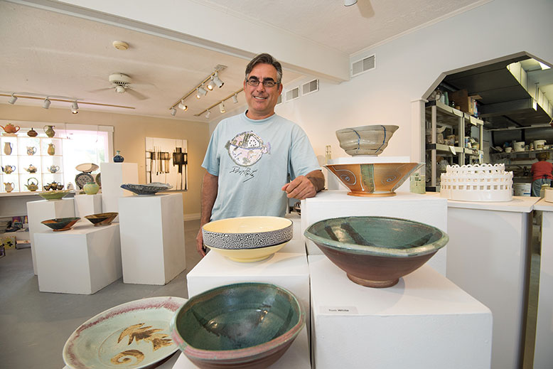 Matt Burton shows off the wares on display at his M.T Burton gallery in Surf City.