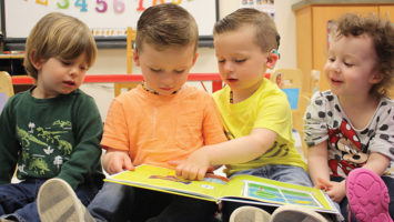 Children reading a picture book together in one of the three Sound Start Babies nursery rooms.