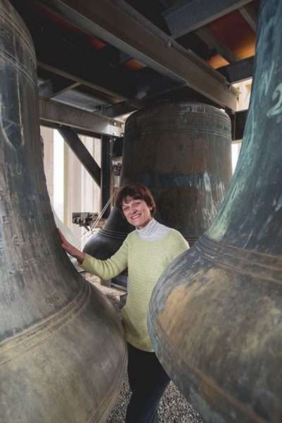 Lisa Lonie stands near the largest bells in Grover Cleveland Tower. When played each Sunday at 1 p.m., the music can be heard up to a mile away.