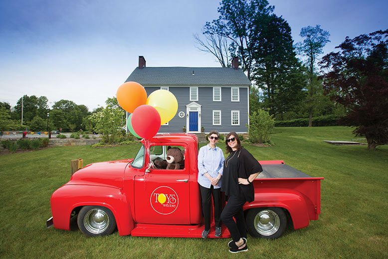 Toys With Love mother/daughter team Gail Rogers, left, and Stacey Rogers with their 1956 delivery truck outside the 1770s farmhouse that serves as their shop.