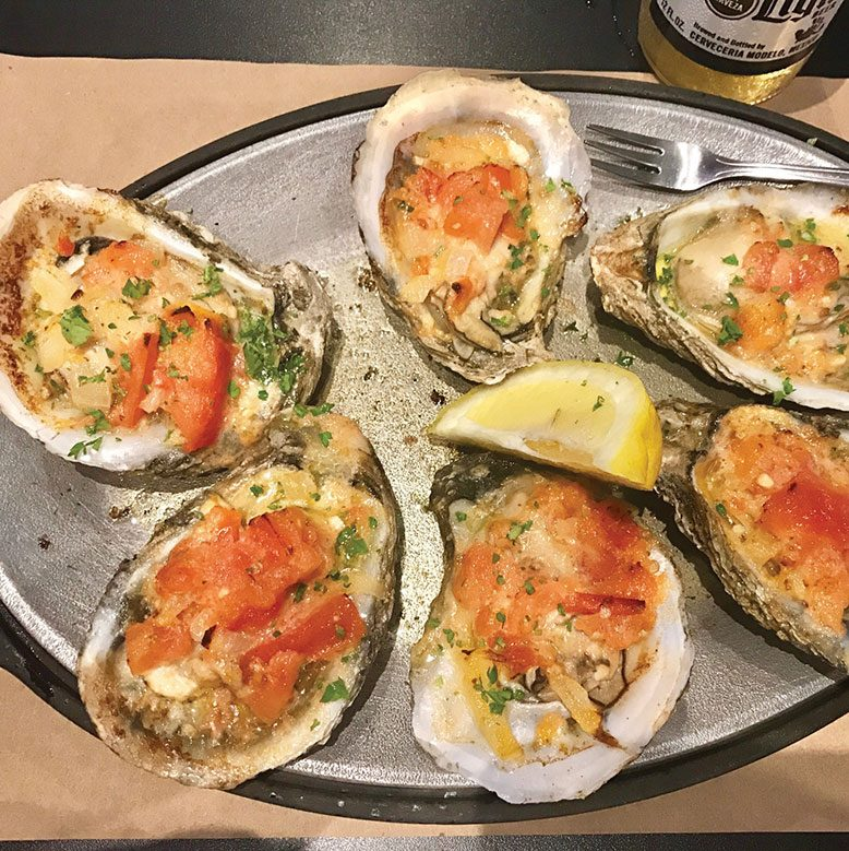 Broiled oysters topped with tomatoes and shallots.